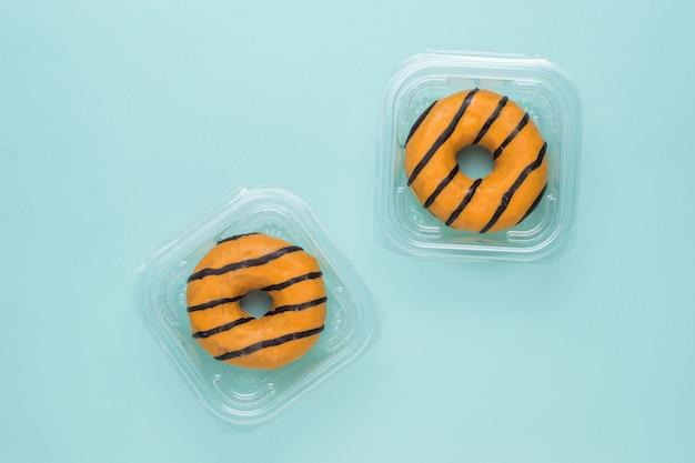 Zwei donuts in plastikboxen zur lieferung verpackt. süßes gebäck mit lieferung nach hause.