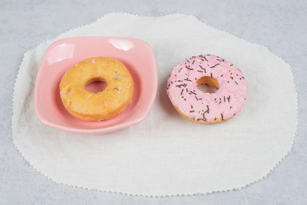 Zwei donuts mit sprinklern auf marmortisch. hochwertiges foto
