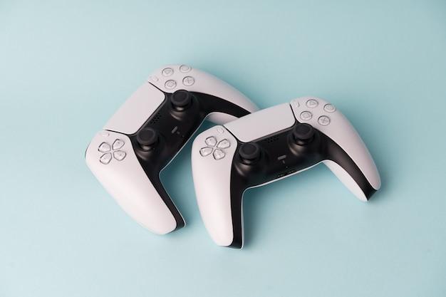 Zwei drahtlose gamepads für videospielkonsolen. blaue wand. minimaler stil.