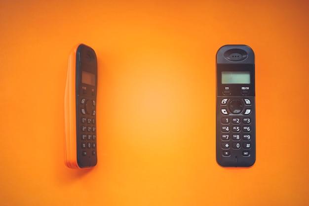 Zwei drahtlose schnurlose telefone, funktelefone, schnurloses dect-telefon auf orangem hintergrund.