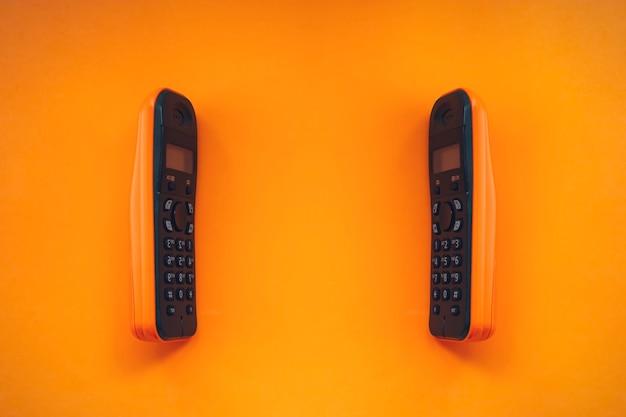 Zwei drahtlose schnurlose telefone, schnurloses telefon dect, funktelefon, funktelefon auf orangem hintergrund.