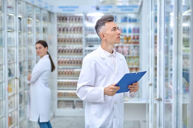 Zwei drogisten führen die routinemäßige inspektion aller arzneimittelbestände durch
