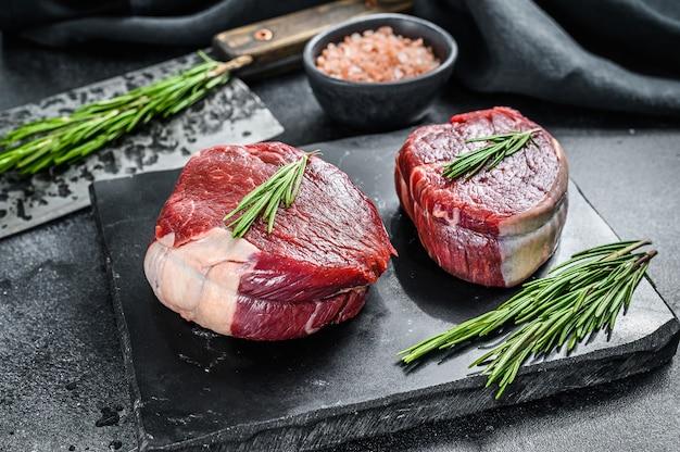 Zwei dünne steakstücke aus dem filet geschnitten. schwarzer hintergrund. draufsicht.