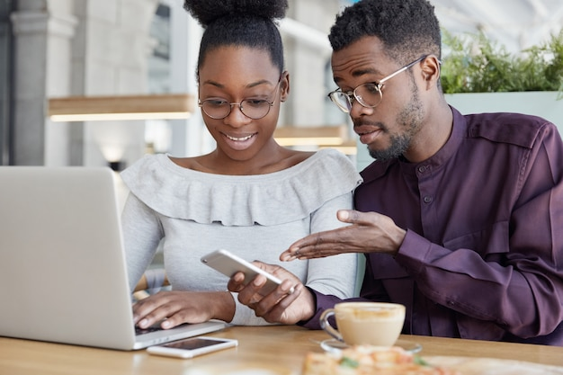 Zwei dunkelhäutige männliche, weibliche verwaltungsmanager überprüfen nachrichten auf dem mobiltelefon, tastatur auf dem laptop, überprüfen informationen