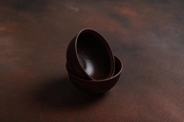 Zwei dunkle handgemachte tonschalen auf braunem tisch