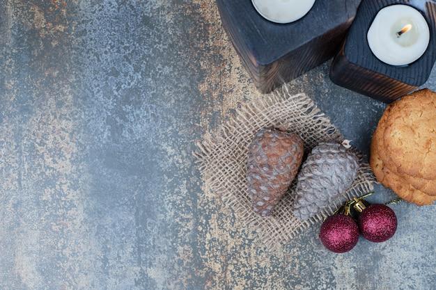 Zwei dunkle kerzen mit keksen, zwei roten kugeln und tannenzapfen auf marmorhintergrund.