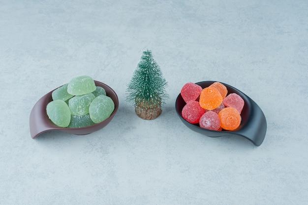 Zwei dunkle platte der zuckermarmelade mit kleinem weihnachtsbaum. hochwertiges foto