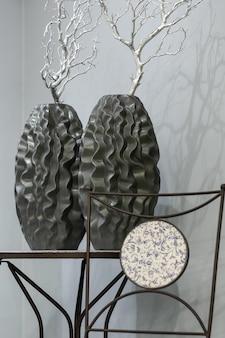 Zwei dunkle vasen mit kurven und einem silbernen ast auf dem tisch vor dem hintergrund einer grauen wand