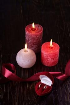 Zwei eheringe in der roten geschenkbox mit kerzenlicht mit drei wachsflammen mit band im dunklen romantischen licht, liebesdatierung, valentinstag, selektiver fokus