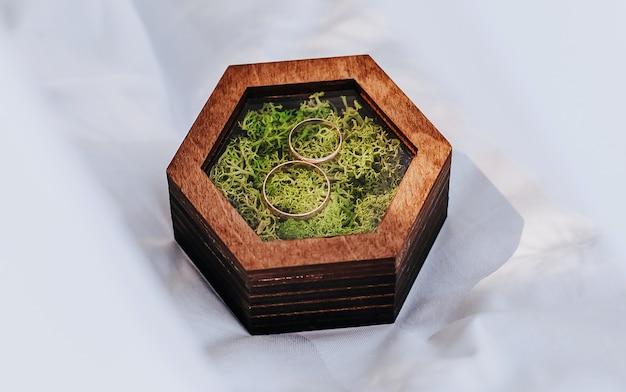 Zwei eheringe in einer holzkiste mit einer moospflanze auf weißem hintergrund mit schleier