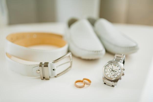 Zwei eheringe mit accessoires für den bräutigam armbanduhr ledergürtel und schuhe auf einem weißen