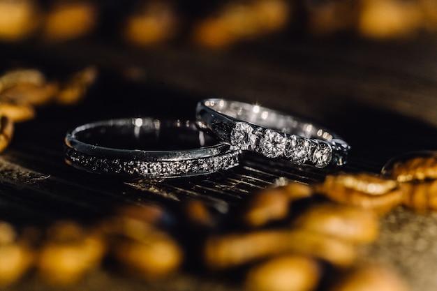 Zwei eheringe mit diamanten auf holzoberfläche