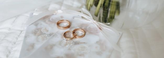 Zwei eheringe und ein verlobungsring liegen auf einer einladung mit blumenhintergrund