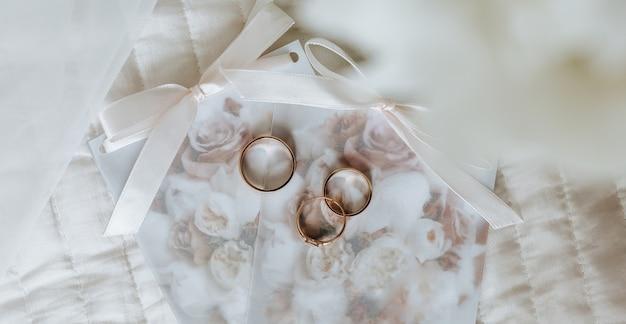 Zwei eheringe und ein verlobungsring liegen auf einer einladung mit blumenwand