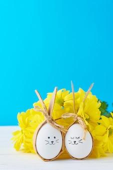 Zwei eier mit zeichnungsgesichtern mit gelben blumen auf einem blauen hintergrund