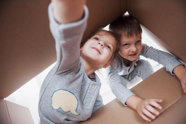 Zwei ein kleinkindjunge und -mädchen, die eine pappschachtel öffnen und mitten in ihr klettern. kinder haben spaß
