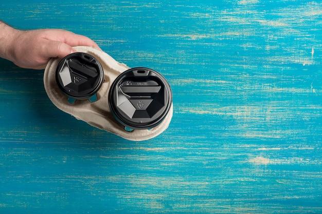 Zwei einweg-pappbecher kaffee und ein becherhalter in männlicher hand auf einer blauen holzoberfläche