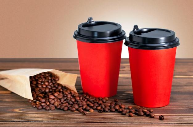 Zwei einwegkaffeetassen und kaffeebohnen