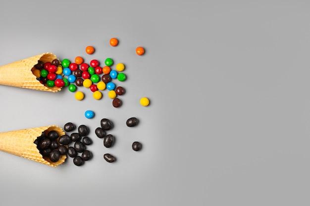 Zwei eistüten mit verschiedenen süßigkeiten auf grauem hintergrund