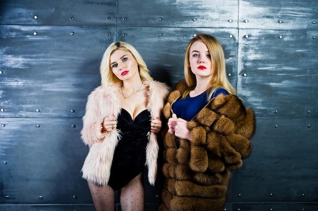 Zwei elegante blonde mädchen tragen auf dem pelzmantel und kombikleid, die gegen stahlwand auf studio aufgeworfen werden.