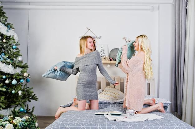 Zwei elegante blonde mädchen tragen auf dem warmen kittel, der auf bett sitzt und spielen mit kissen gegen baum.
