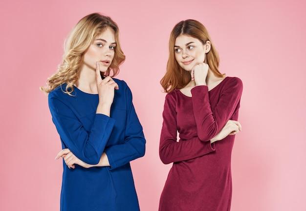 Zwei elegante frauen in kleidern mode freundin luxus rosa hintergrund. hochwertiges foto