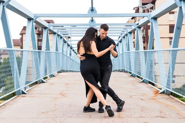 Zwei elegante tangotänzer auf brücke