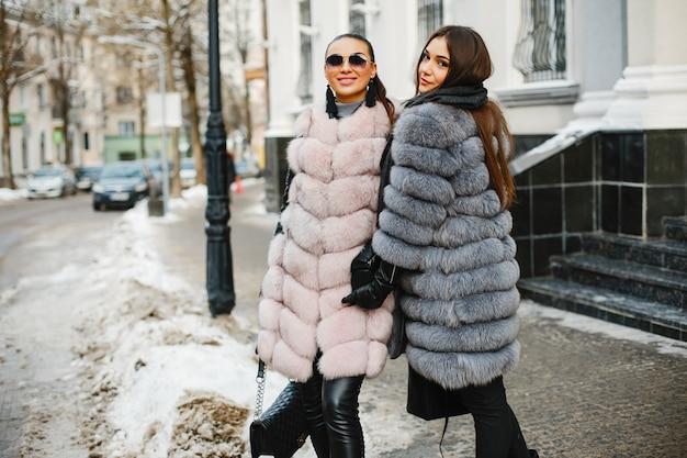 Zwei elegante und großartige mädchen in den stilvollen pelzmänteln, die in die winterstadt gehen