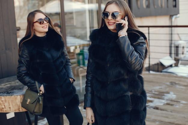 Zwei elegante und stilvolle mädchen, die in einer winterstadt stehen und das telefon verwenden
