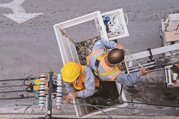Zwei elektriker, die mit drähten arbeiten