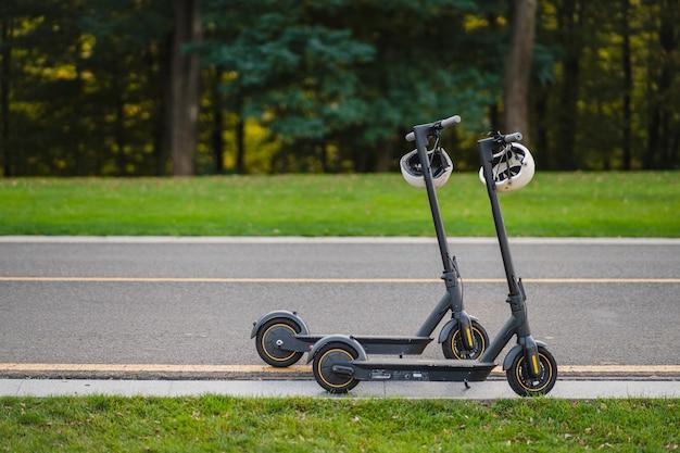 Zwei elektrische tretroller oder e-scooter parkten am straßenrand