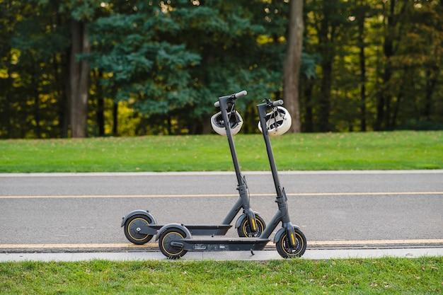 Zwei elektrische tretroller oder e-scooter parkten an der seitenstraße