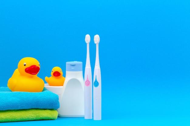Zwei elektrische zahnbürsten und zubehör für bad auf blauem hintergrund.