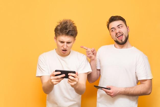 Zwei emotionale freunde treten in spielen auf dem smartphone gegeneinander an