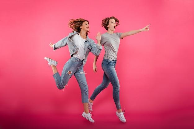 Zwei emotionale springende und zeigende freundinnen.