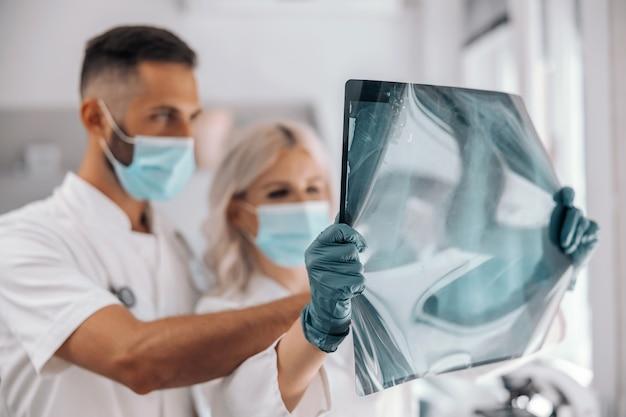 Zwei engagierte, fleißige, intelligente kollegen, die röntgenaufnahmen der lunge des patienten halten und diese betrachten.