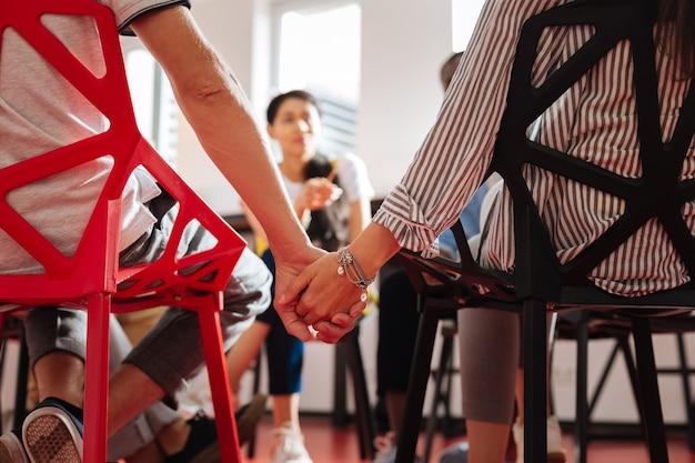 Zwei enge leute. junge nervöse leute, die ihre hände halten, während sie an der psychologischen sitzung teilnehmen