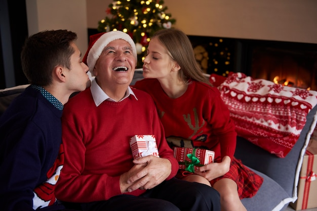 Zwei enkelkinder küssen ihren großvater