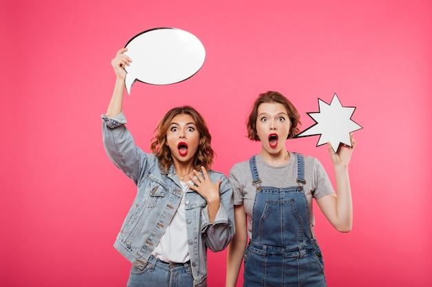 Zwei entsetzte freundinnen, die spracheblasen halten.