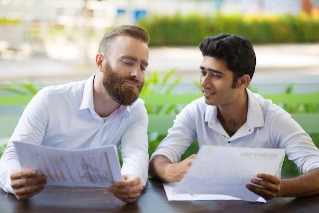 Zwei entspannte geschäftsleute, die im café im freien sich treffen und arbeiten