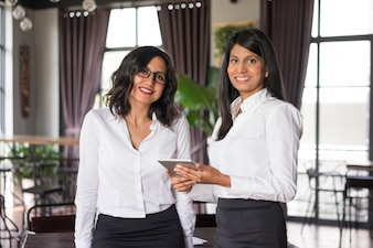 Zwei entspannte weibliche Kollegen, die Tablet-Computer im Café verwenden.