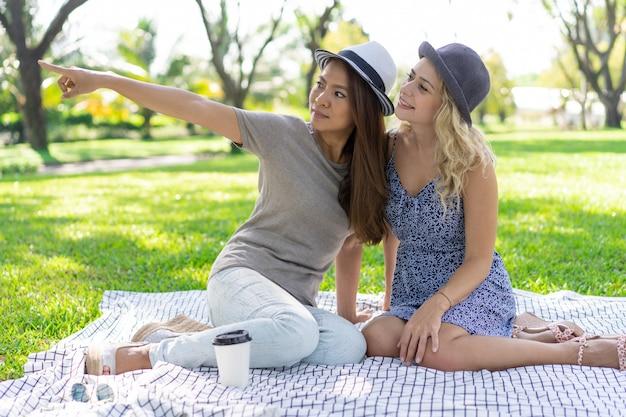 Zwei entspannten schönheiten, die auf decke im park sitzen
