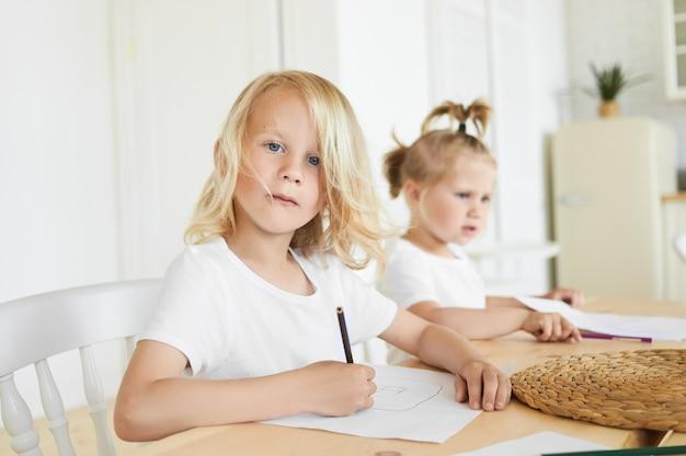 Zwei entzückende kaukasische kinder, die zusammen hausaufgaben am holztisch machen. netter siebenjähriger junge mit blonden haaren und blauen augen, die zu hause zeichnen, während seine kleine kleine schwester sitzt