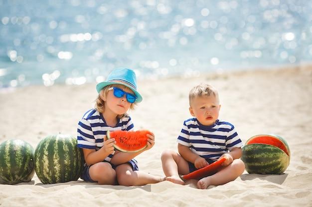 Zwei entzückende kinder, die am seeufer sitzen und wassermelone essen. zwei brüder, die spaß am strand haben. hübsche kleine jungs draußen