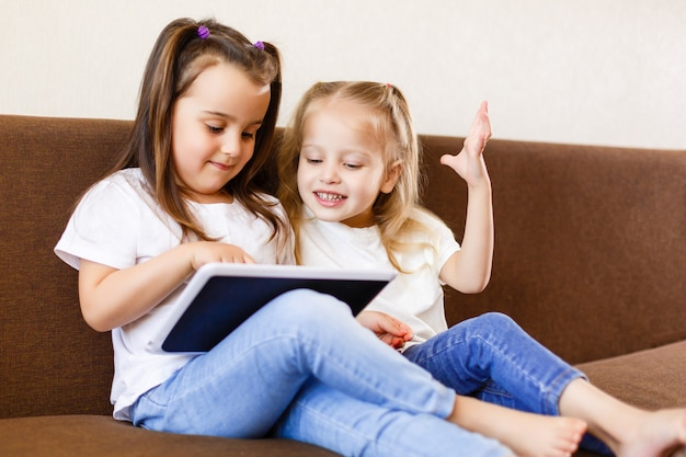 Zwei entzückende kleine schwestern, die zu hause mit einer digitalen lächelnden schwester der tablette mit tabletten-pc-computer spielen