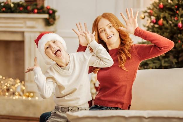 Zwei erbsen in einer hülse. fröhliche mutter und sohn machen lustige gesichter, während sie über weihnachten aufgeregt werden.