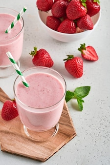 Zwei erdbeer-smoothie oder milchshake mit beeren und minze im glas auf hellrosa hintergrund. sommergetränkshake, milchshake und erfrischungs-bio-konzept. gesunde ernährung, vegetarisches lebensmittelkonzept.