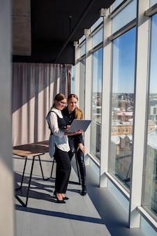 Zwei erfolgreiche architektinnen unterhalten sich am fenster mit einem laptop über ein gemeinsames projekt. junge wirtschaftswissenschaftlerinnen in formeller kleidung sprechen während einer arbeitspause