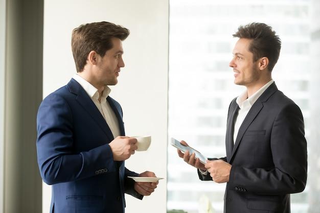 Zwei erfolgreiche geschäftsmänner, die geschäft besprechen