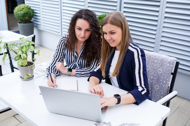 Zwei erfolgreiche junge geschäftsfrauen sitzen an einem tisch mit laptop und notebook und arbeiten an einem neuen entwicklungsprojekt, studentinnen schreiben einen bericht über die arbeit ihres computers